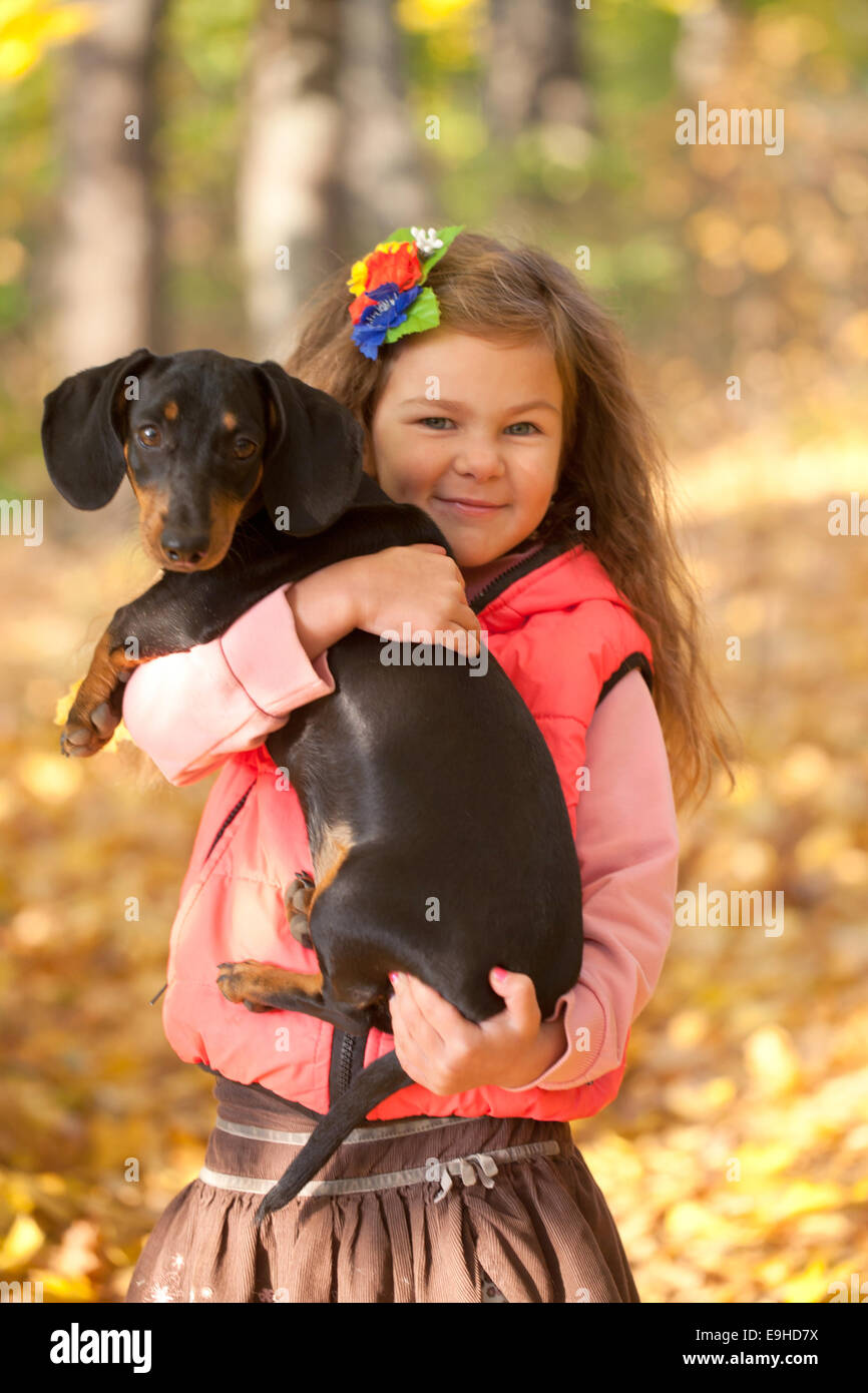 Little kid with a dachshund puppy. Girl and dog cuddling - Stock Image
