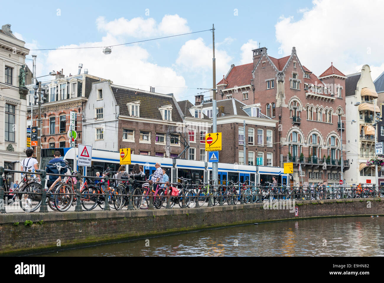 Bicycles locked to the railings along a canal in the city of Amsterdam, Netherlands - Stock Image