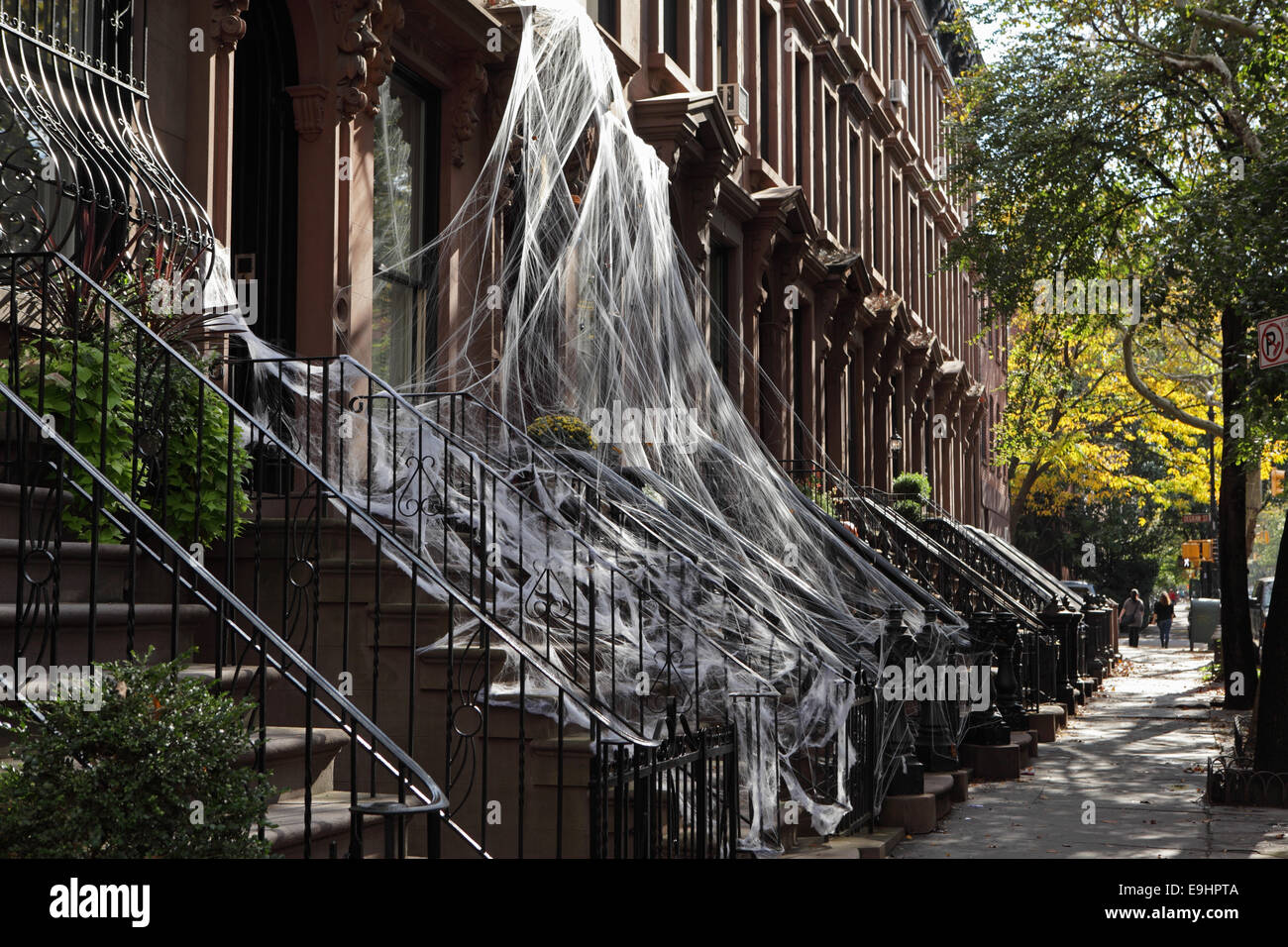 Brooklyn brownstone townhouses in Carroll Gardens draped in spiderweb Halloween decoration - Stock Image