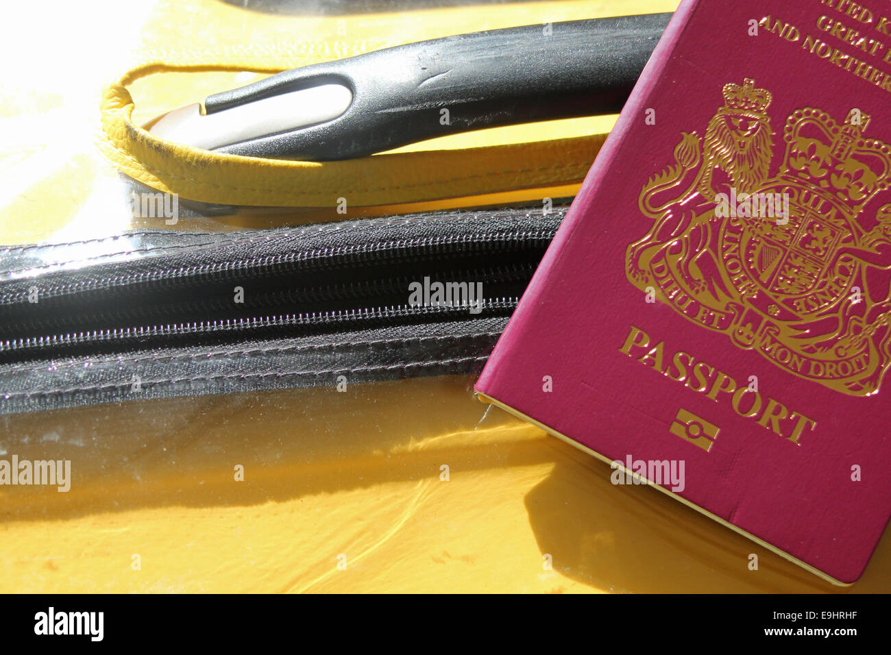 Passport and suitcase symbolizing vacation and travel - Stock Image