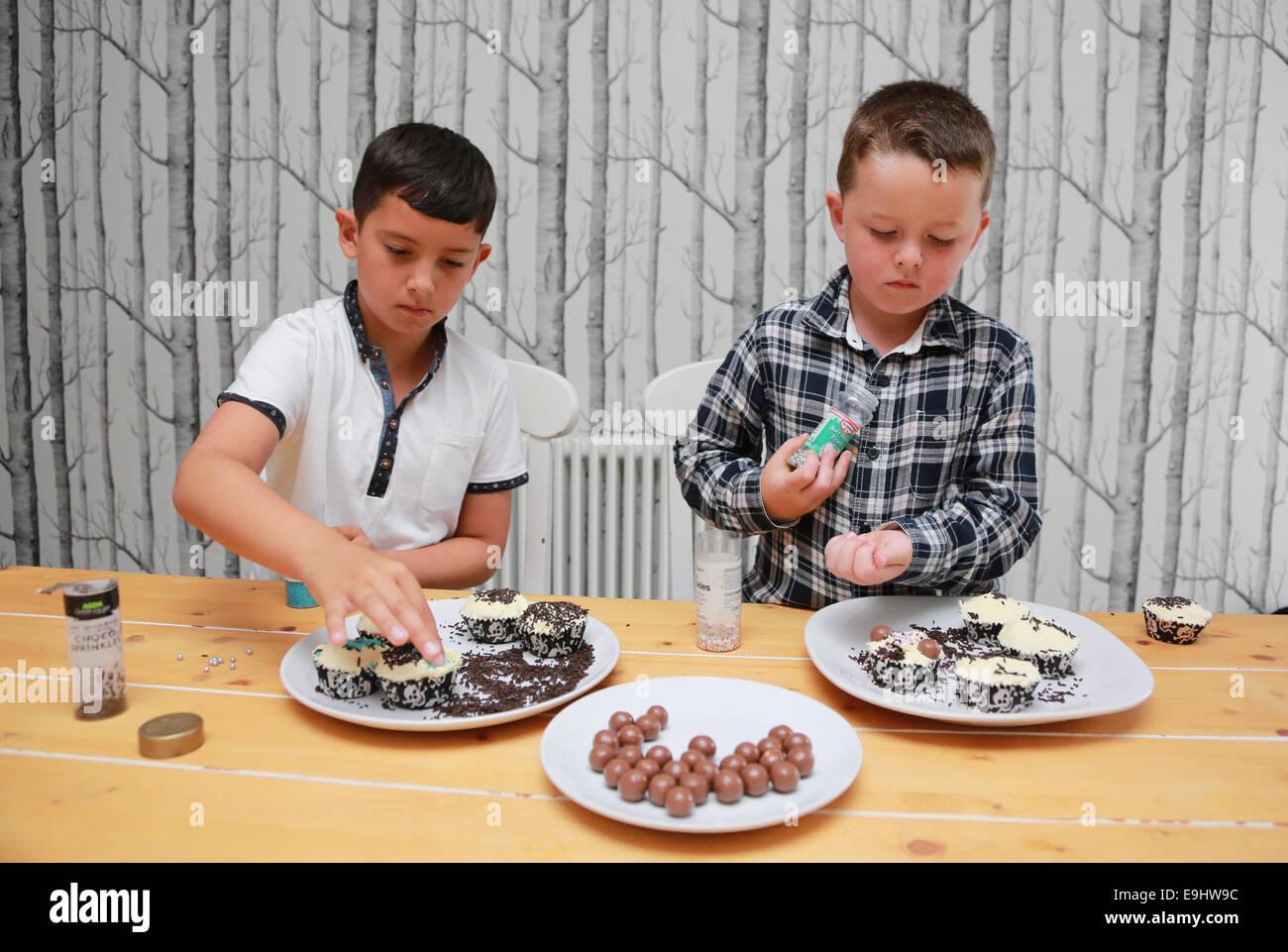 Children decorating cakes Stock Photo