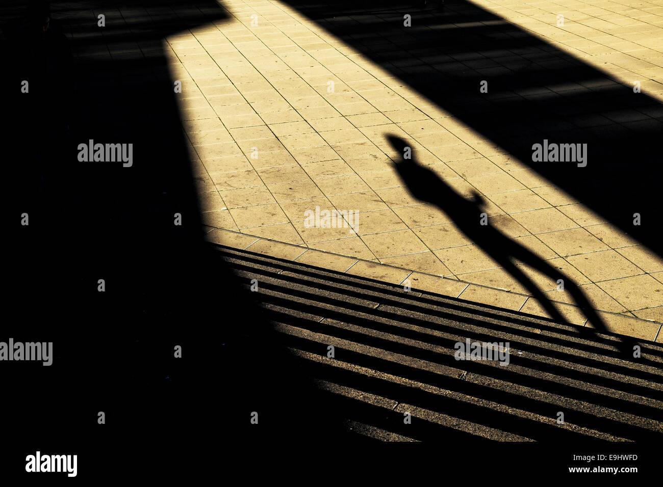 Basildon, Essex, UK. 28 October 2014.  Unseasonal warm sunshine casting shadows of shoppers in Basildon Town Centre. - Stock Image