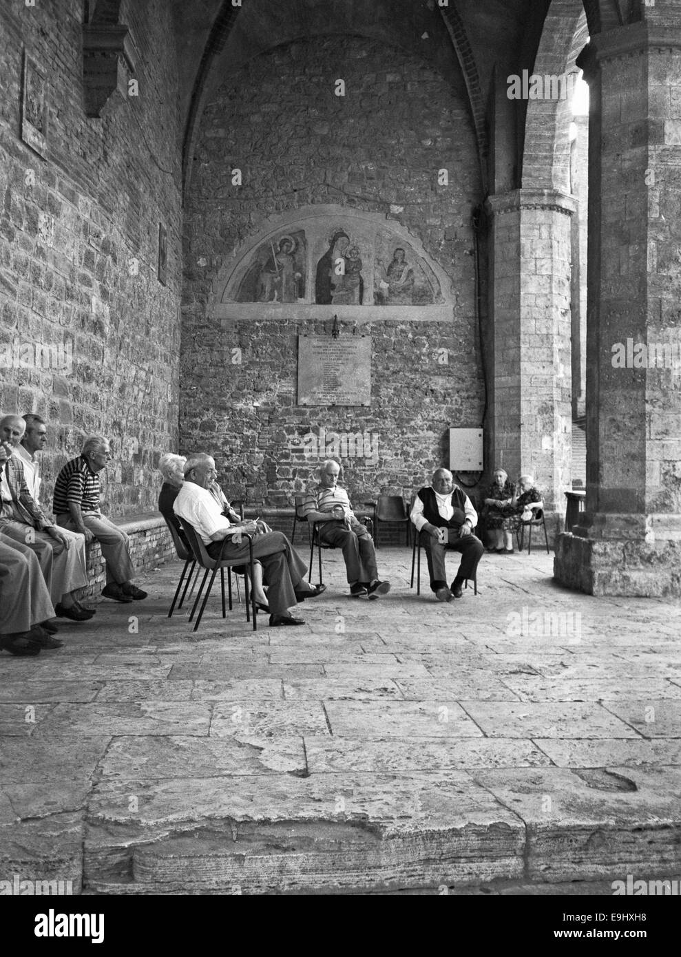 Older men relaxing in San Gimignano in Central Tuscany - Stock Image