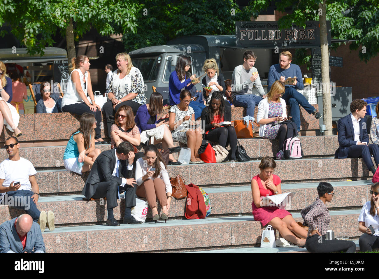 City workers London Broadgate lunch sitting sunshine - Stock Image