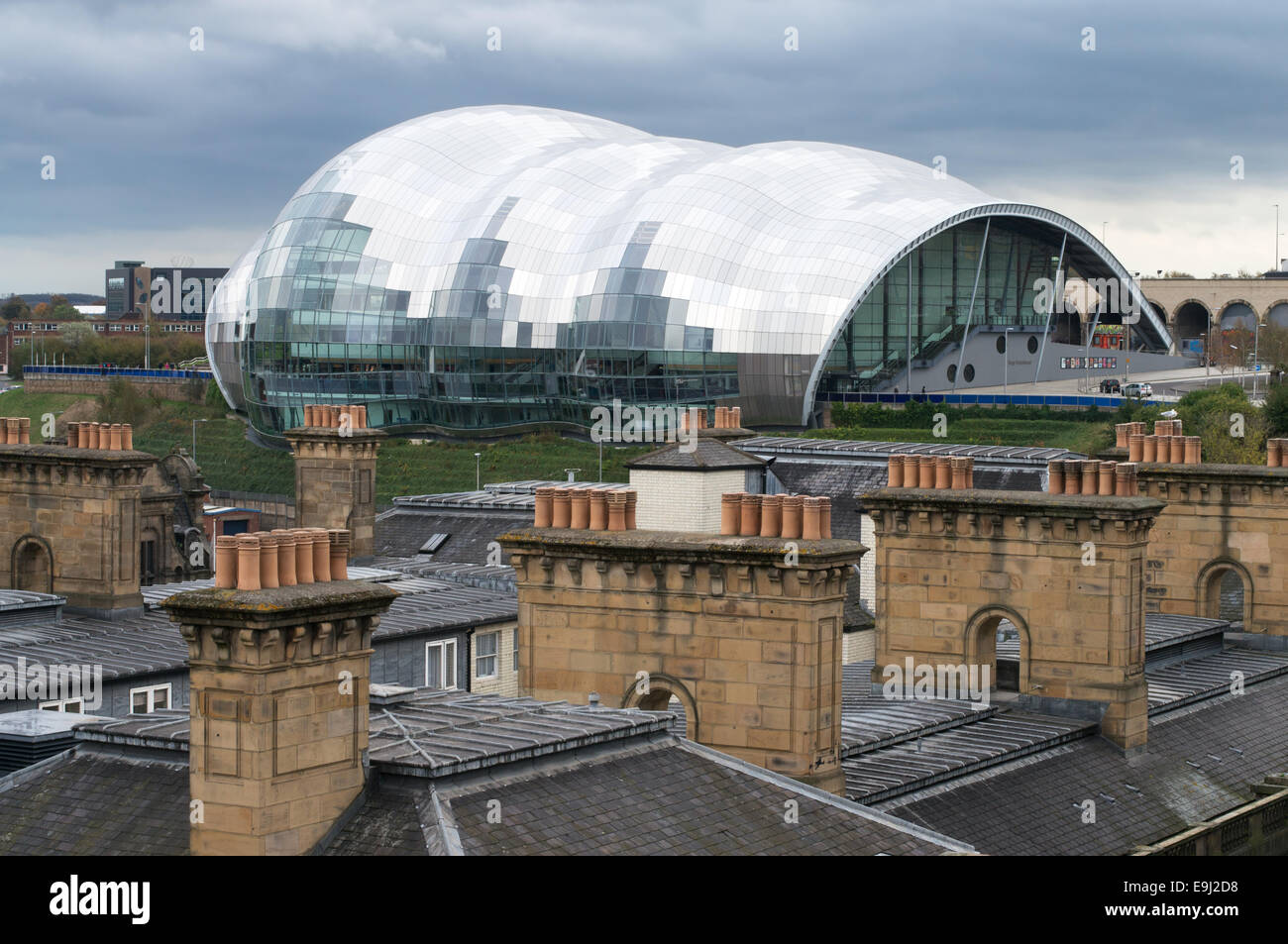 The Sage concert hall in Gateshead seen across a row of chimney pots north east England UK - Stock Image