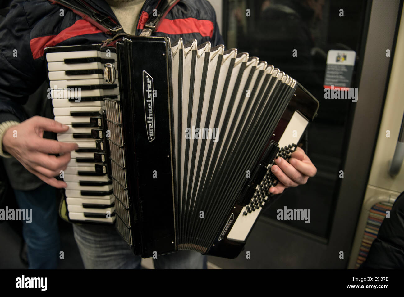 an accordion player busks on the paris metro trains with a traditional wind instrument - Stock Image