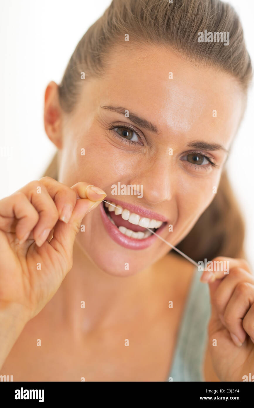 Portrait of young woman using dental floss - Stock Image