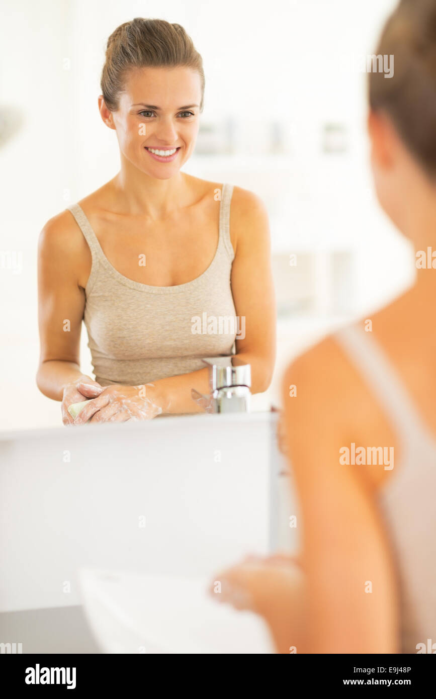 Happy young woman washing hands in bathroom - Stock Image