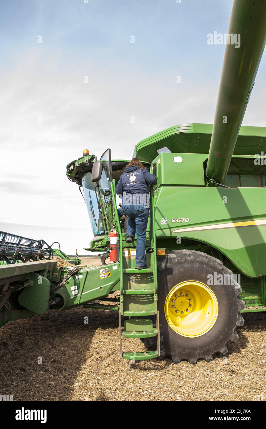 Mature woman climbing into the cab on a John Deere S670