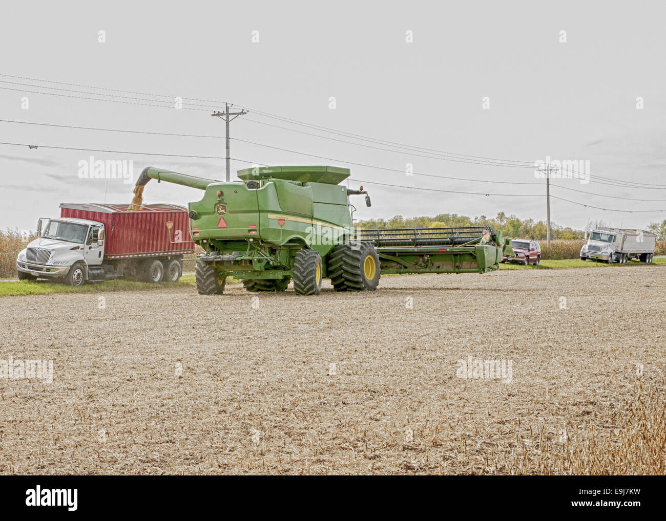 John Deere S670 combine is dumping its soybean load from the hopper into a waiting truck. - Stock Image