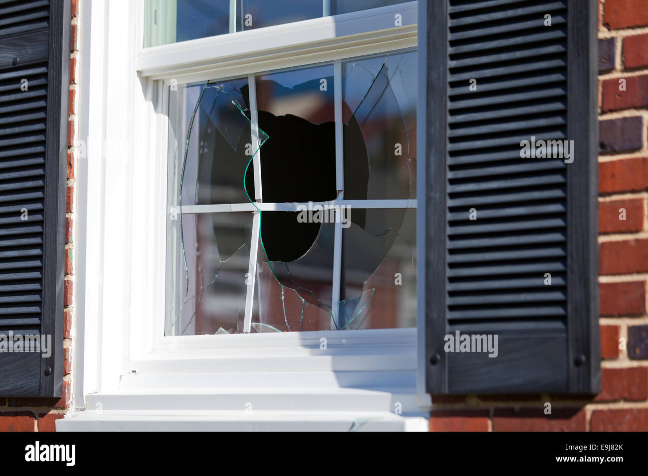 Broken window of family home - USA - Stock Image