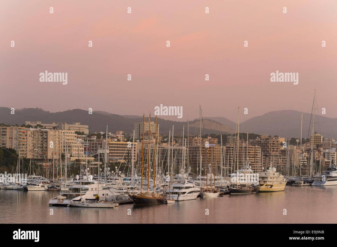 Boats and holiday apartments on the coast at Palma de Mallorca in Palma, Spain, at sunrise sunset. Stock Photo