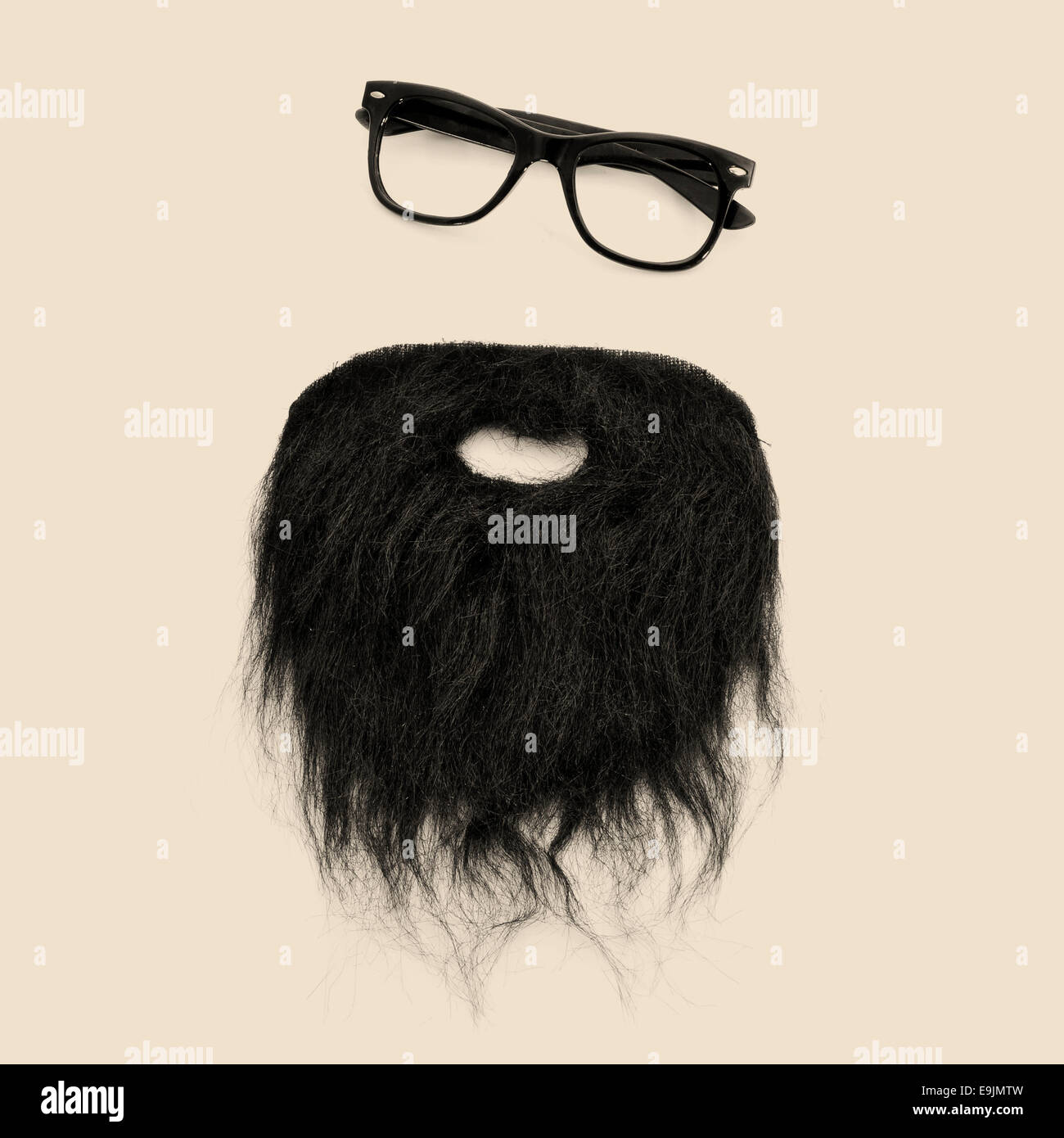 a pair of retro eyeglasses and a beard forming a man face on a beige background - Stock Image