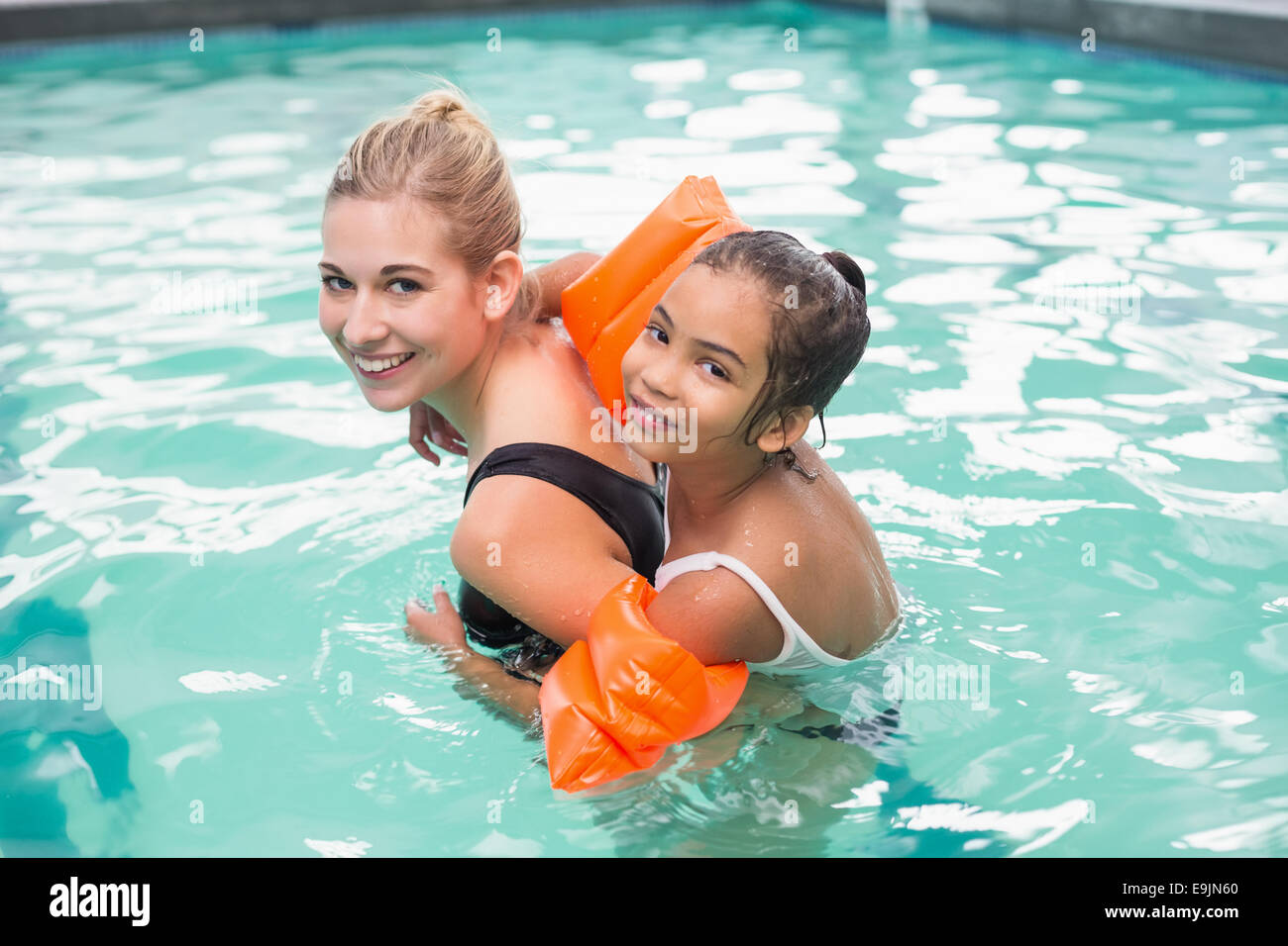 Cute little girl getting a piggy back from swimming coach - Stock Image