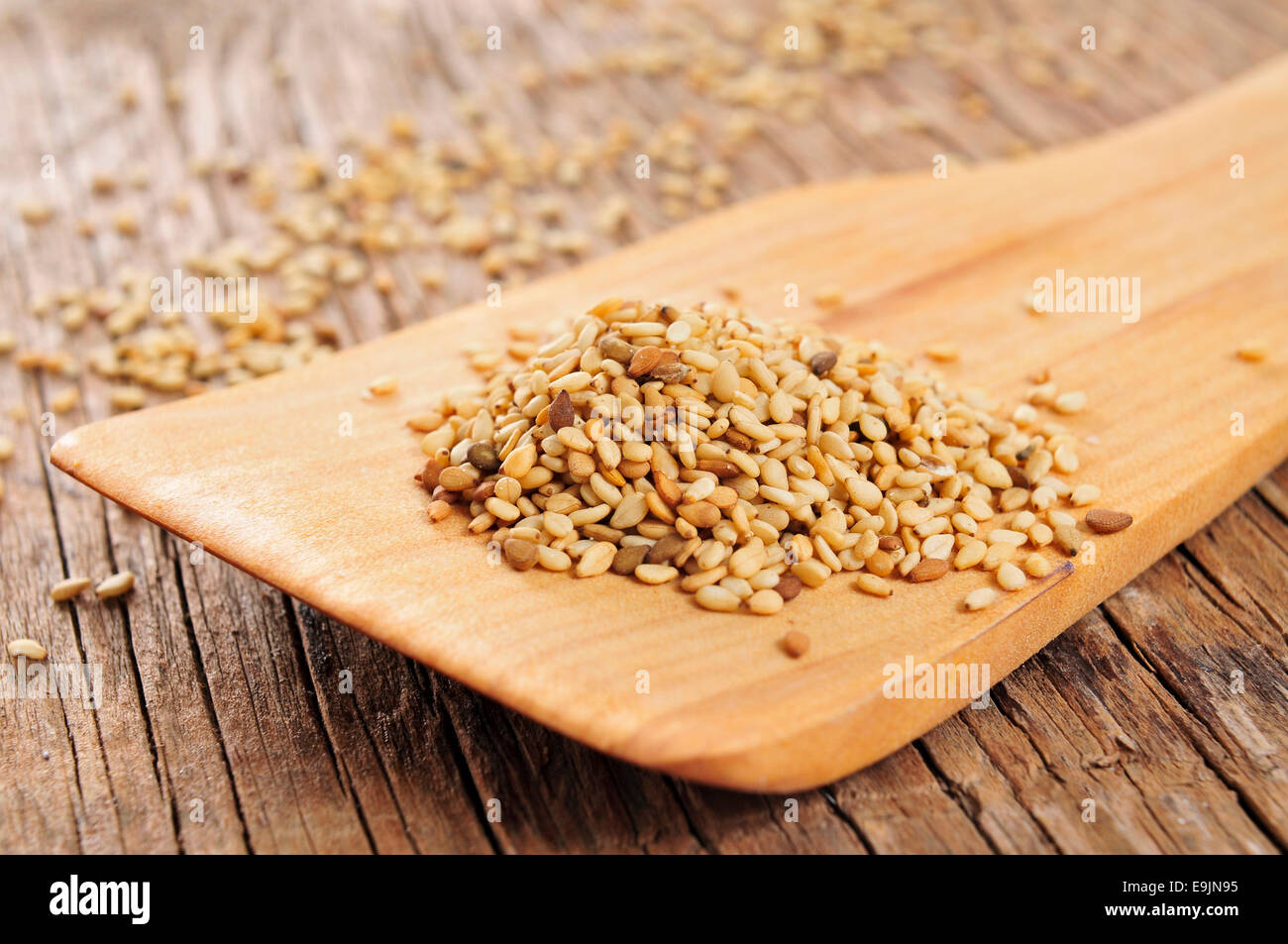 sesame seeds in a wooden spatula on a rustic wooden table - Stock Image