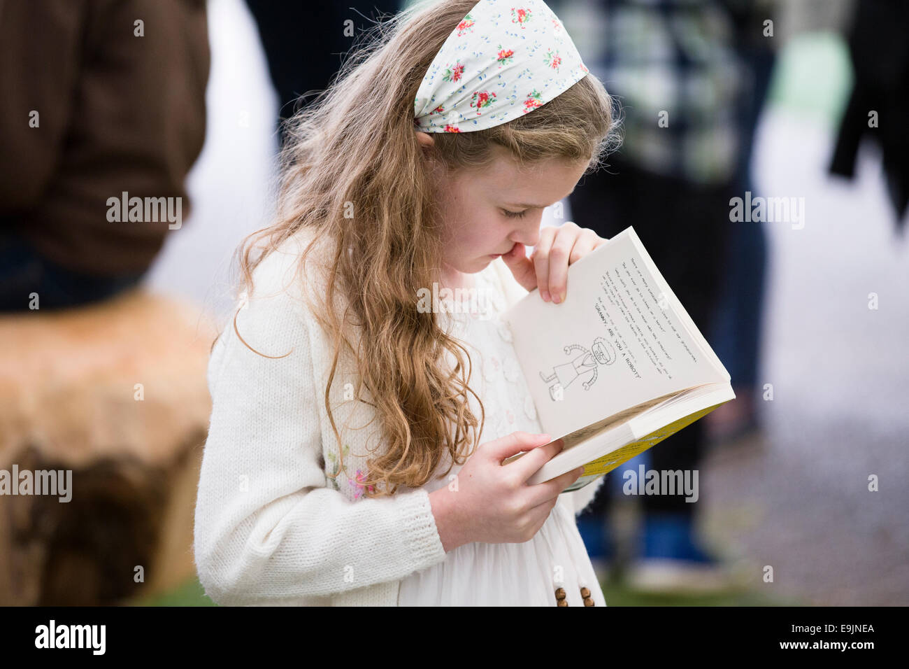 A girl reading a book at the Cheltenham Literature Festival in the UK - Stock Image