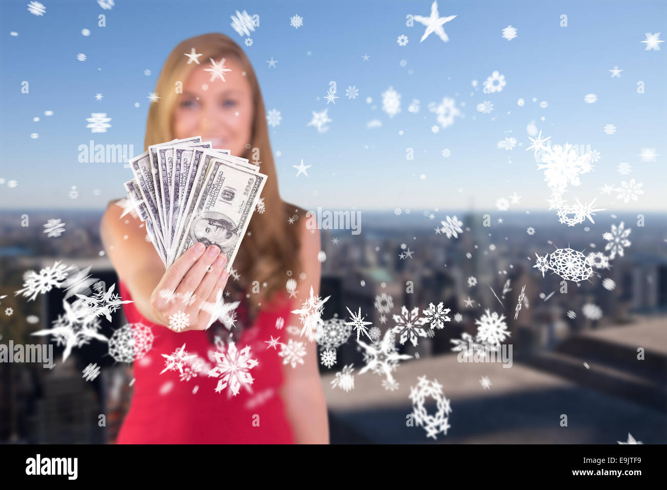 Composite image of pretty blonde showing wad of cash - Stock Image
