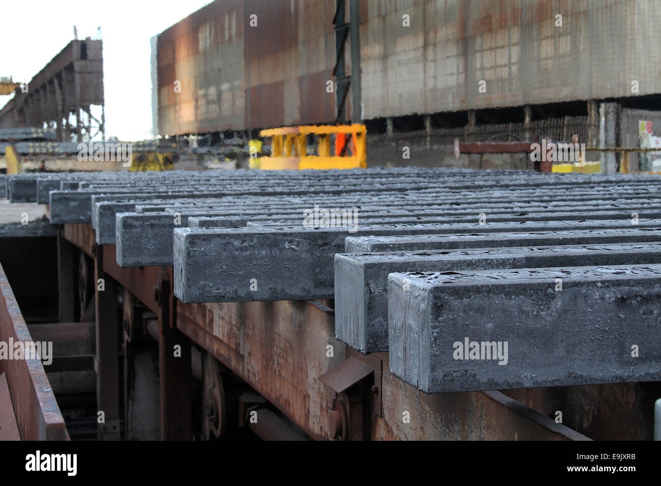 Hot steel bars from continuous casting machine on cooling bank. - Stock Image