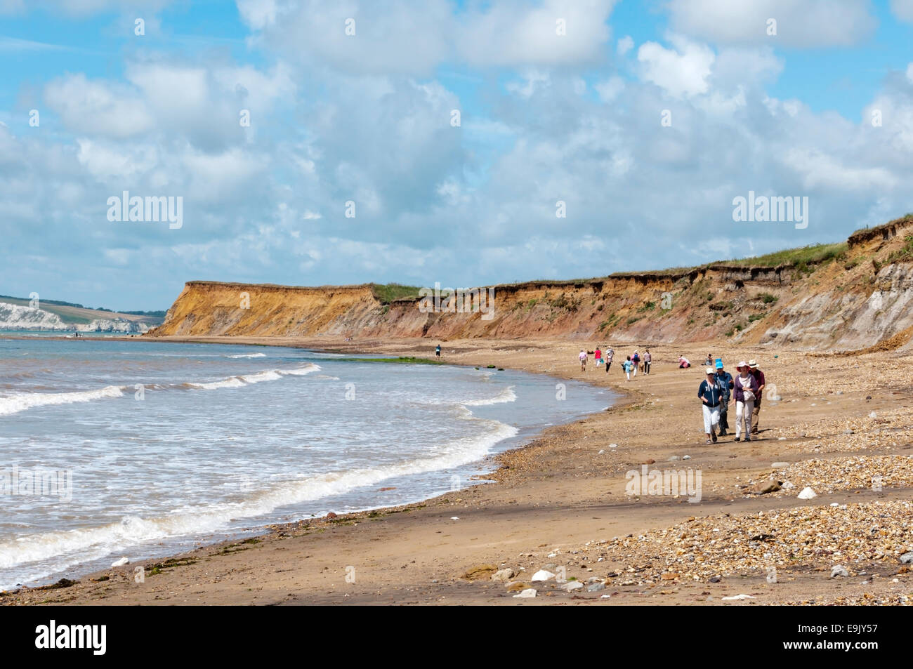 Holidaymakers walking along the beach at Brook Bay on the south coast of the Isle of Wight. - Stock Image