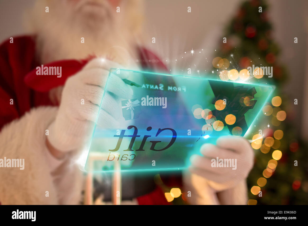 Composite image of santa using futuristic touchscreen - Stock Image