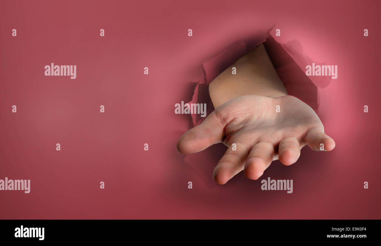 Composite image of hand bursting through paper - Stock Image
