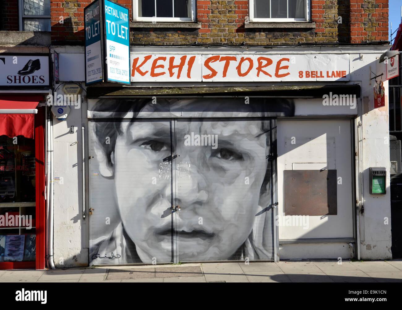 A derelict business premises in Bell Lane, Spitalfields, London covered in street art grafitti - Stock Image