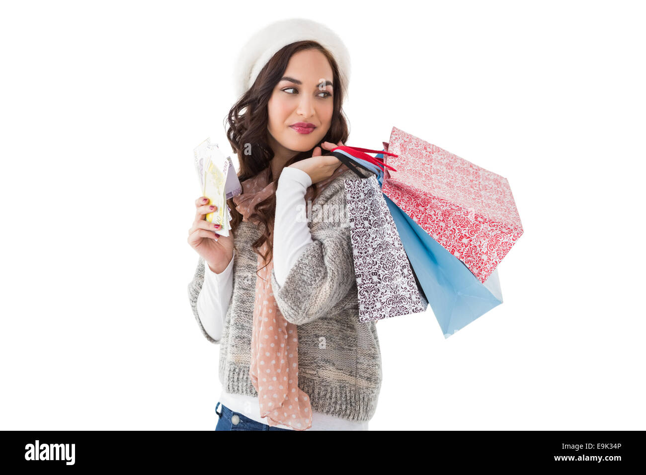 Brunette holding cash and shopping bags - Stock Image