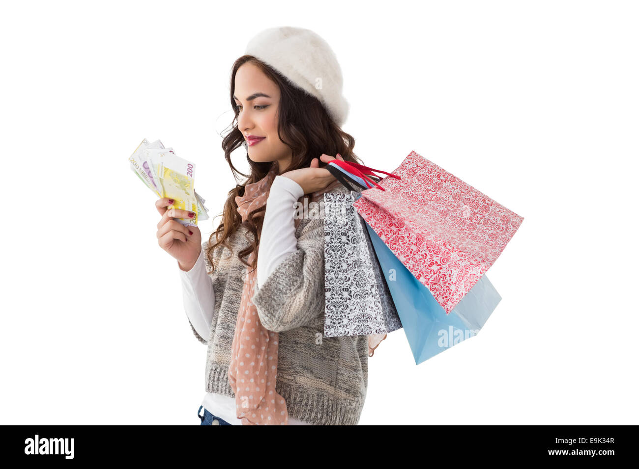 Happy brunette holding cash and shopping bags - Stock Image