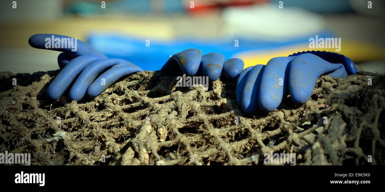 rubber gloves on fishing net - Stock Image