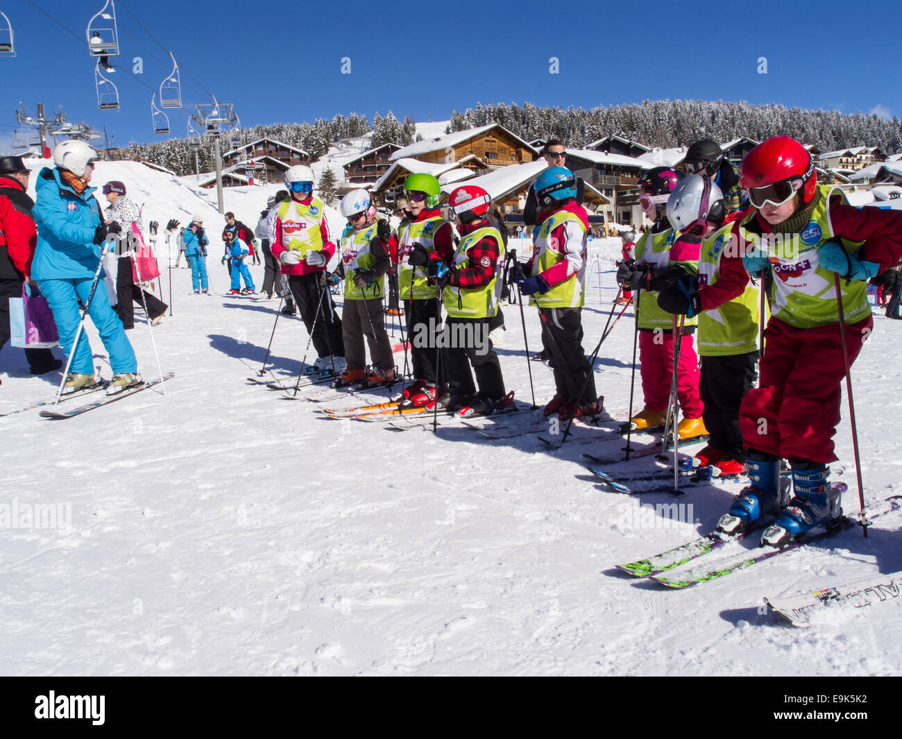 group of children on  skis wearing ski clothes and helmets departing for a  skiing lesson with a ski instructor - Stock Image