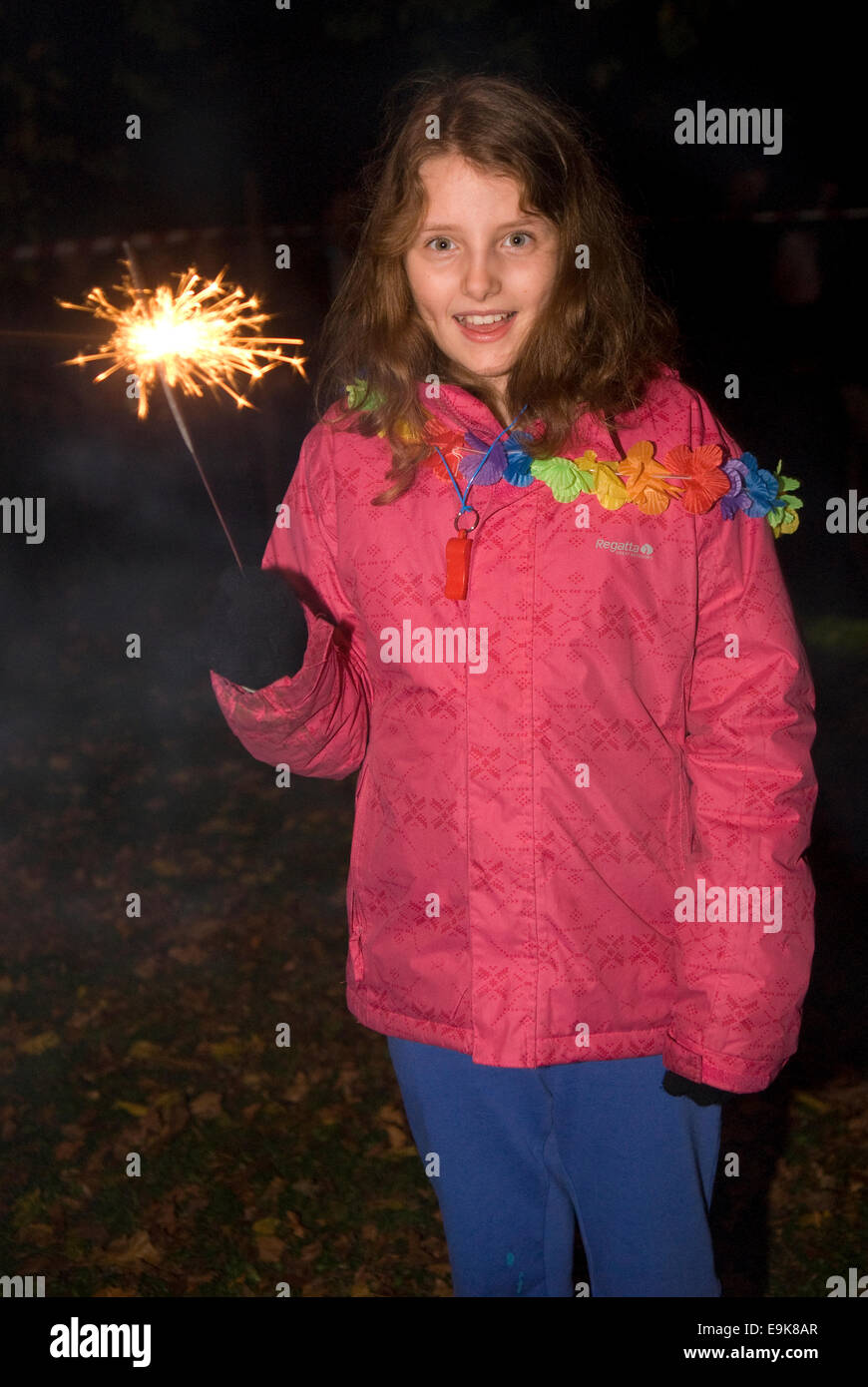 Young girl playing with sparkler at the end of Liphook Carnival, 25 October 2014, Liphook, Hampshire, UK. Stock Photo