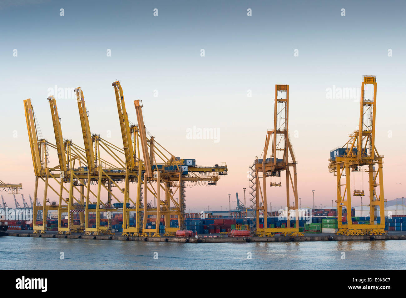Yellow cranes move shipping containers at Barcelona's main port - Port de Barcelona - at sunrise. - Stock Image