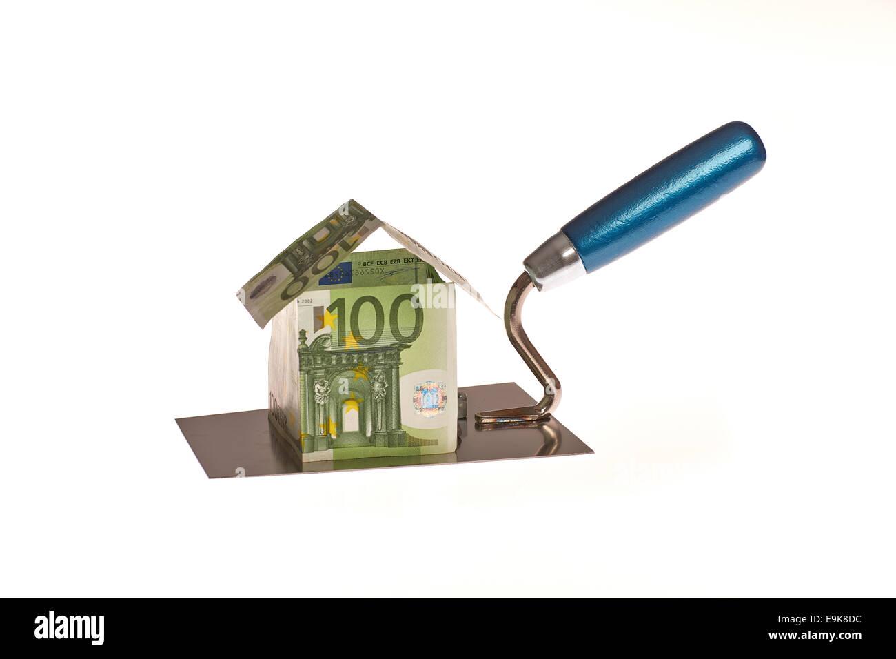 Haus aus Euro Geld auf einer Maurer Kellle - Stock Image