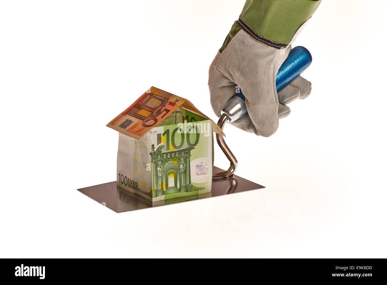 Hausbau aus Euro Geld auf einer Maurer Kelle - Stock Image