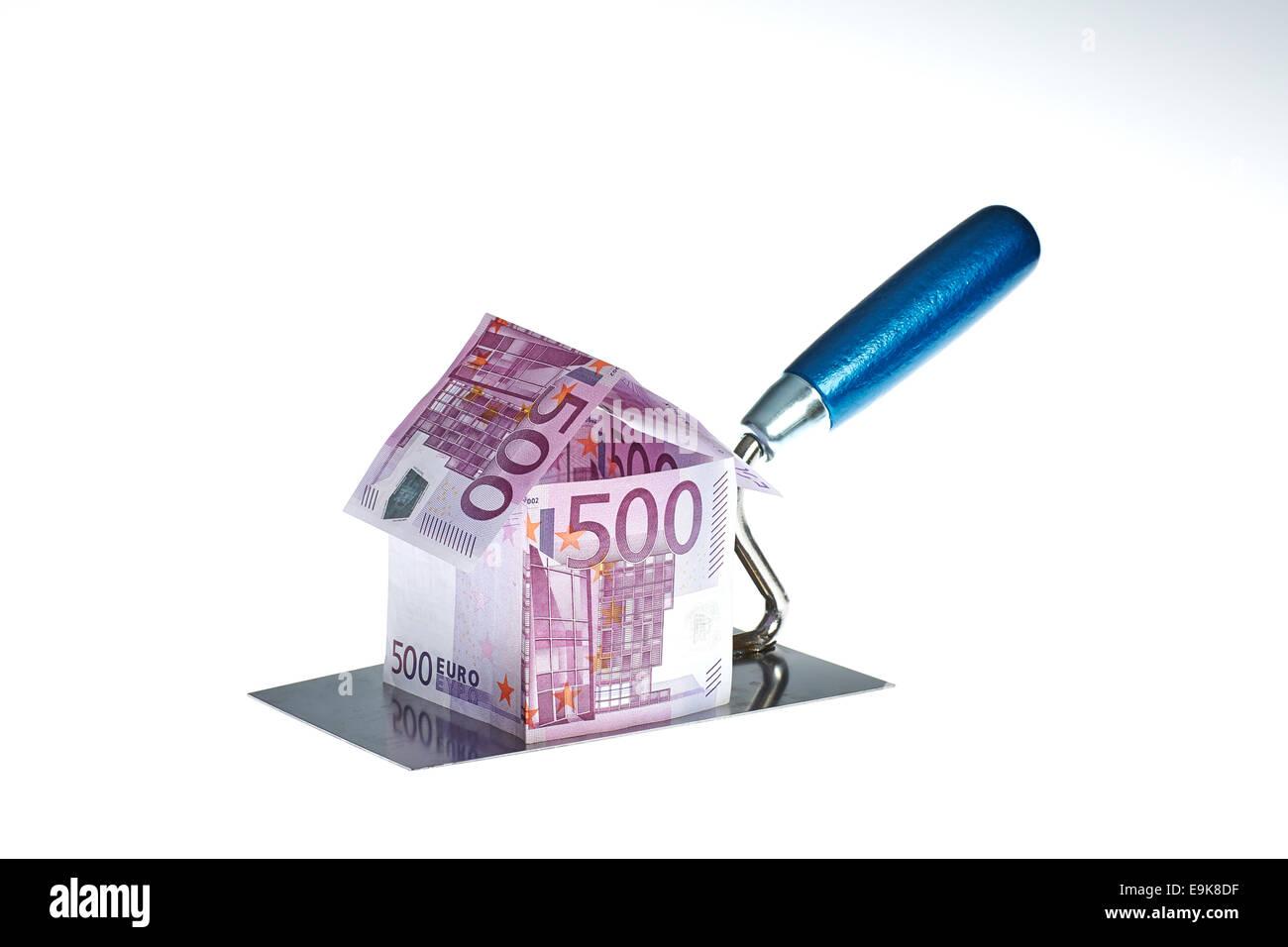 Haus gebaut aus Euro Geldschein auf Handwerker Kelle - Stock Image