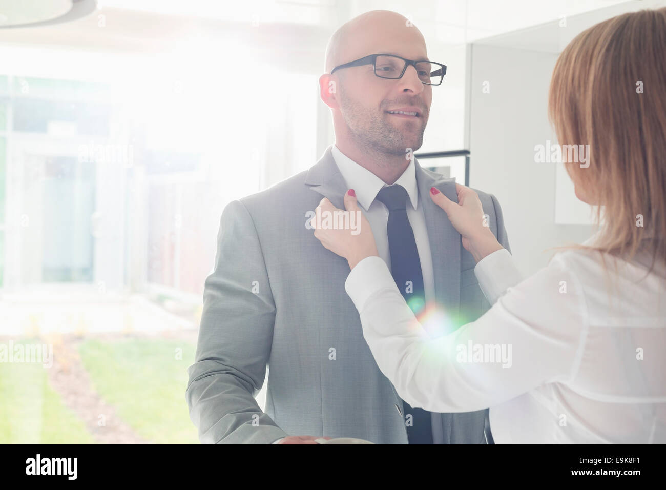 Woman dressing up businessman at home - Stock Image
