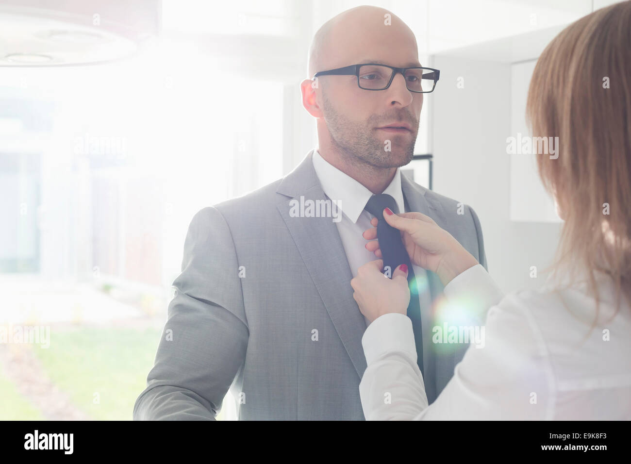 Woman adjusting businessman's tie at home - Stock Image