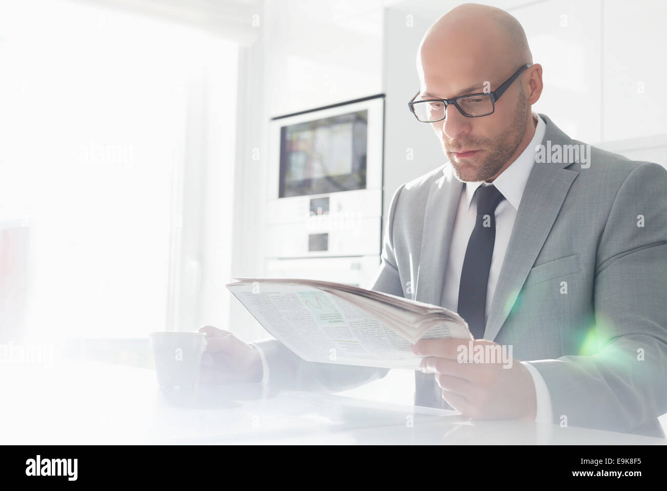 Mid adult businessman having coffee while reading newspaper at home - Stock Image