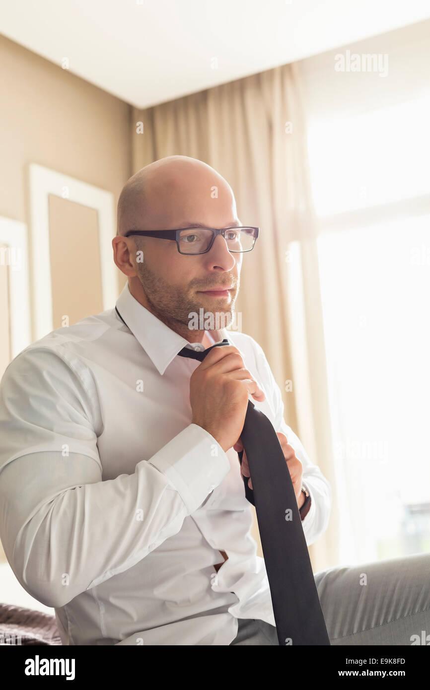 Mid adult businessman adjusting necktie at home - Stock Image