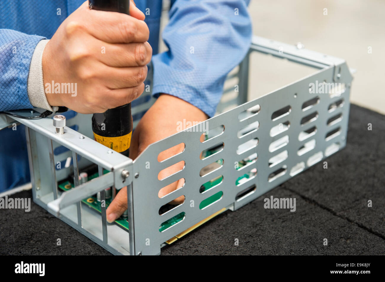 Midsection of male engineer repairing computer part in electronics industry - Stock Image
