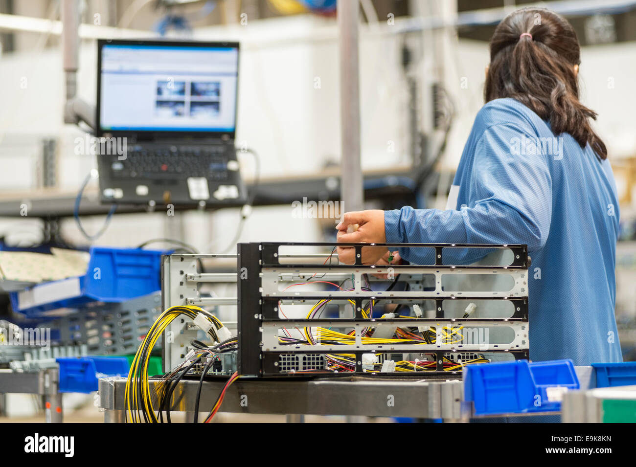 Rear view of female technician repairing computer part in electronics industry - Stock Image