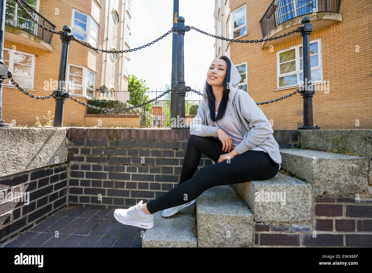 Full length portrait of young woman sitting on stairs against building - Stock Image