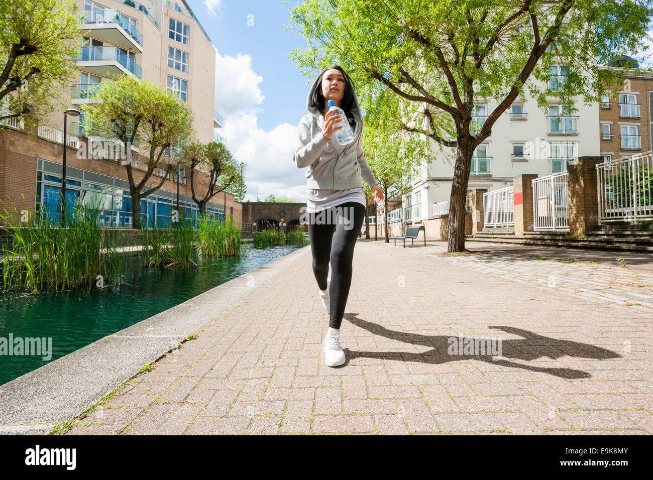 Full length of fit young woman jogging by canal against buildings - Stock Image