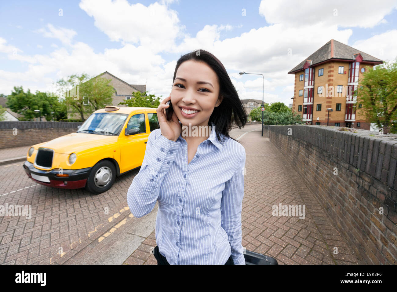 Portrait of smiling businesswoman answering cell phone on sidewalk with taxi in background Stock Photo