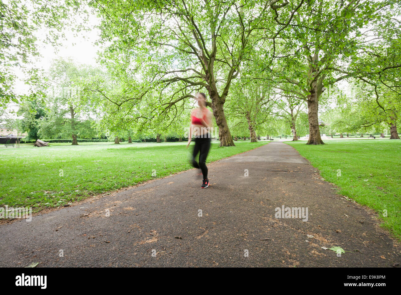 Blurred motion of woman jogging in park - Stock Image