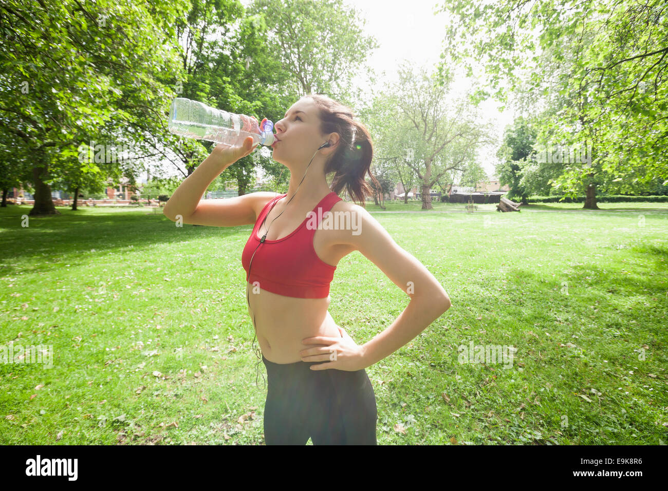 Fit woman drinking water while listening to music in park - Stock Image