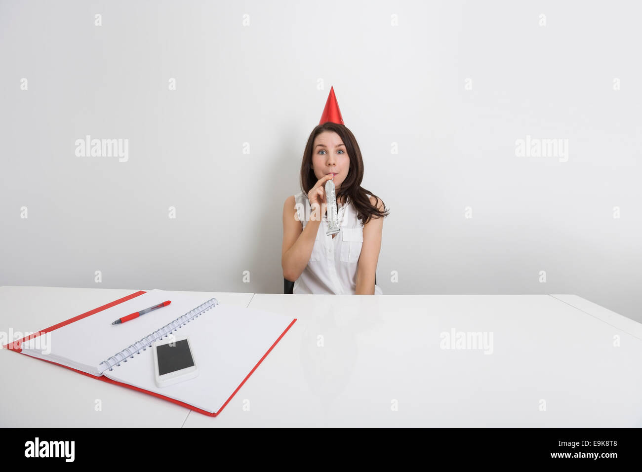 Portrait of happy businesswoman in party hat blowing horn at desk in office - Stock Image