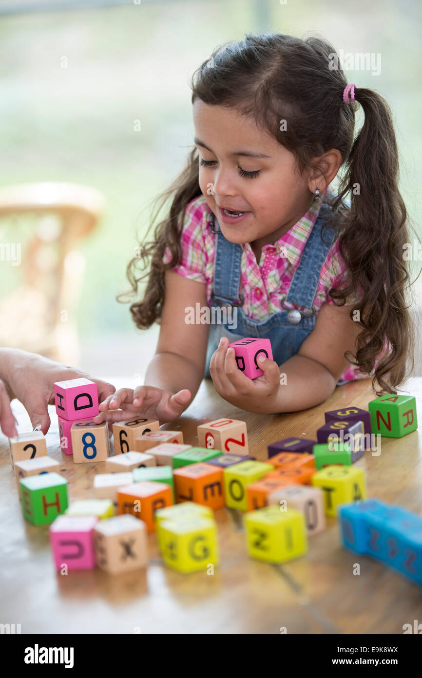 Happy girl playing with alphabet blocks at table - Stock Image