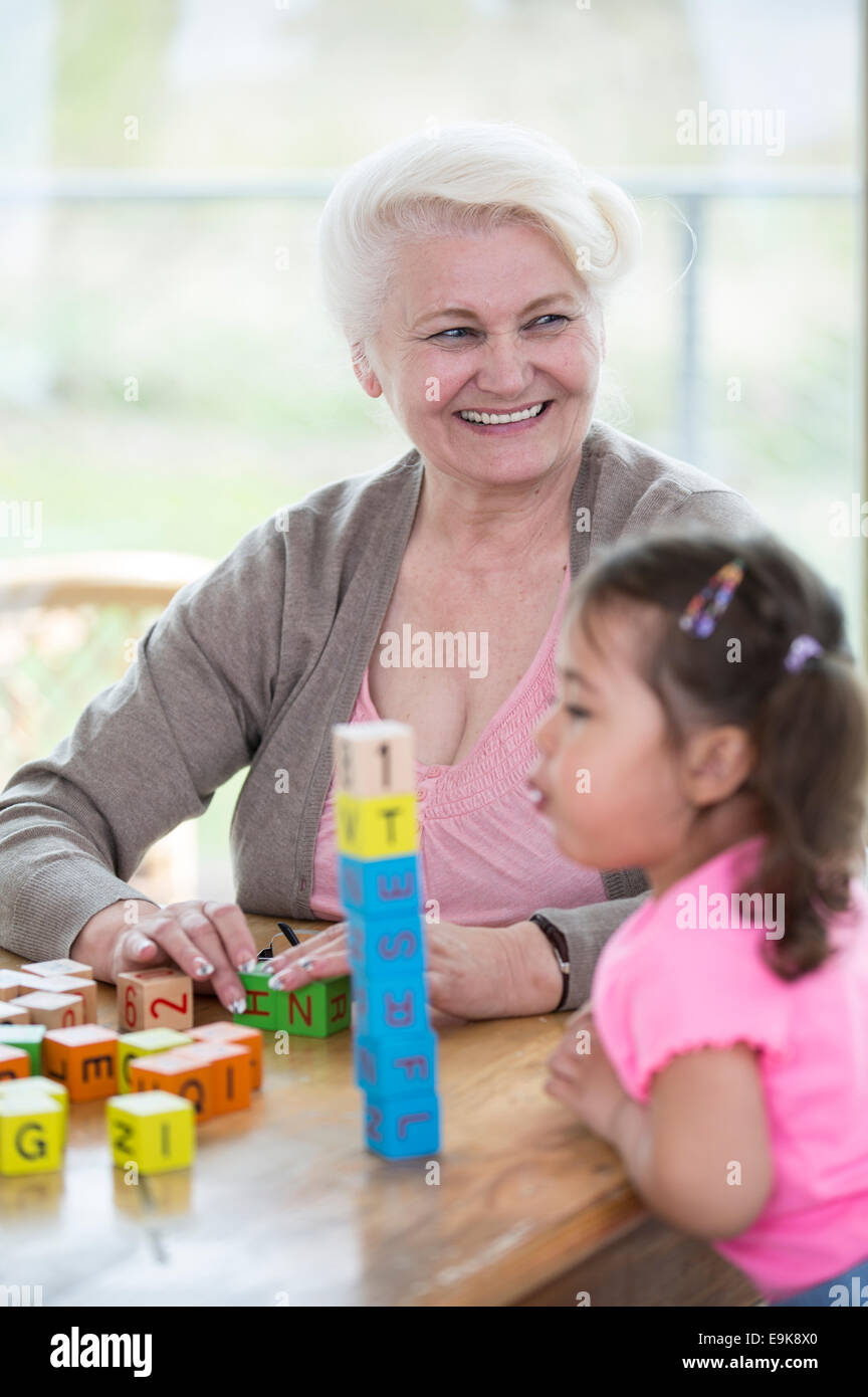 Happy grandmother looking away while granddaughter blowing stacked alphabet blocks in house - Stock Image