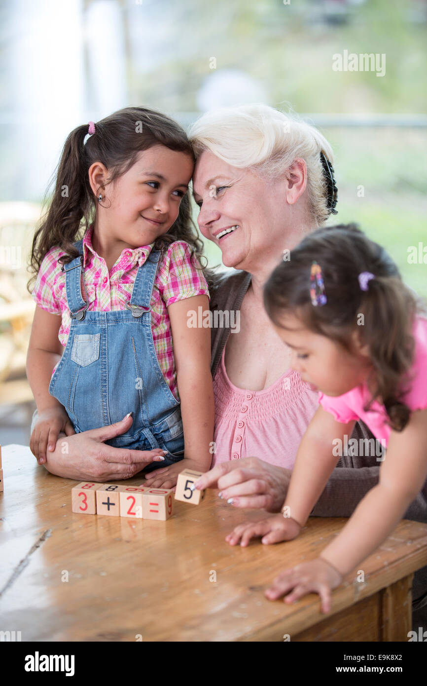 Loving grandmother teaching calculation to granddaughters at table in house - Stock Image